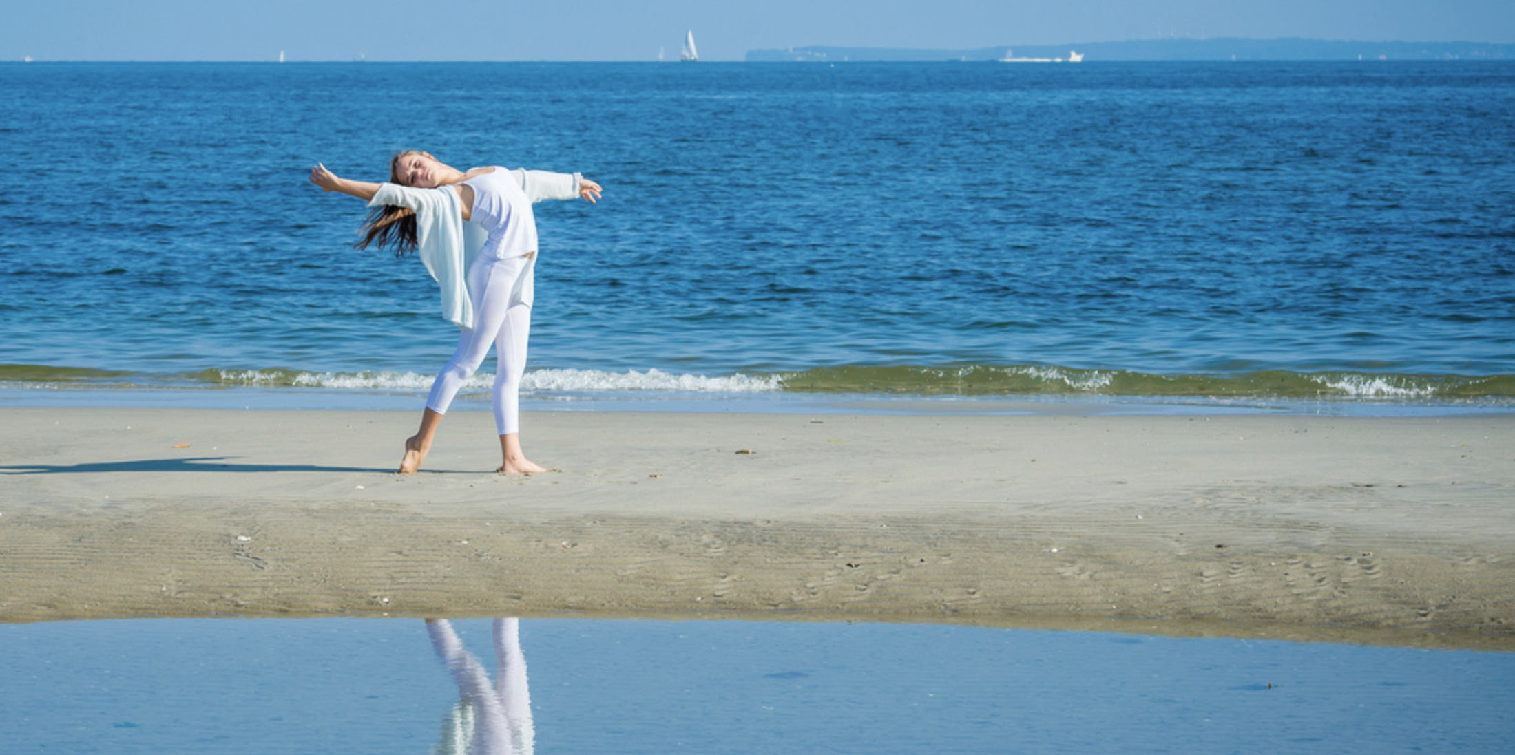Young girl dancing beside beach for family pictures by family photographer in Omaha, NE Paula Moser Photography.
